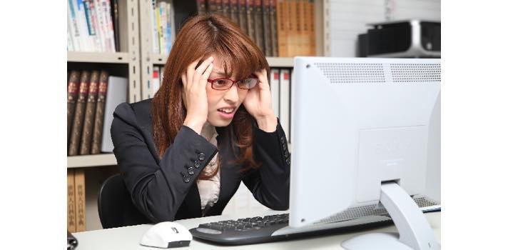 悩む女性とパソコン