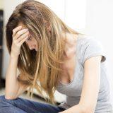 頭を抱えて悩む女性